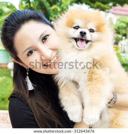 Happy woman and dog in her house - stock photo