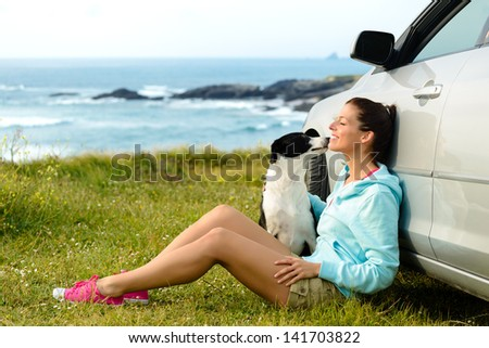Happy woman and dog sitting outside car on summer travel vacation. Pet and human friendship and traveling concept. Relaxing and enjoying peace on nature together. - stock photo