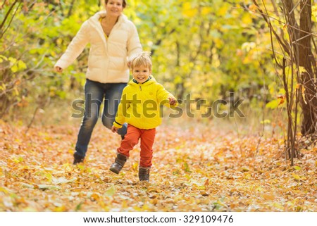 Happy woman and her little son having fun in autumn park - stock photo