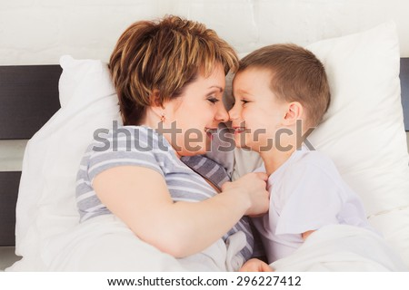 Happy woman and her son enjoying each other in  bedroom