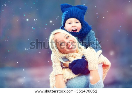 happy woman and kid embracing under winter snow - stock photo