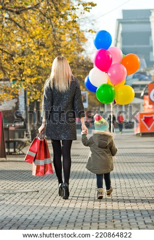 happy woman and little child with red shopping bag and air-balloons, walking on street - stock photo