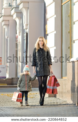 happy woman and little child with red shopping bag, walking on street - stock photo
