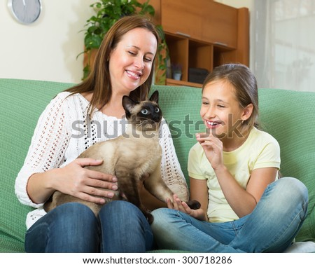 Happy woman and little daughter sitting with cat at home