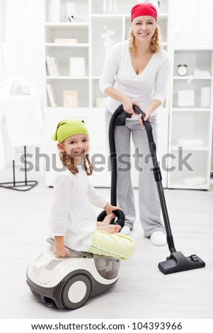 Happy woman and little girl cleaning the room using a vacuum cleaner - stock photo