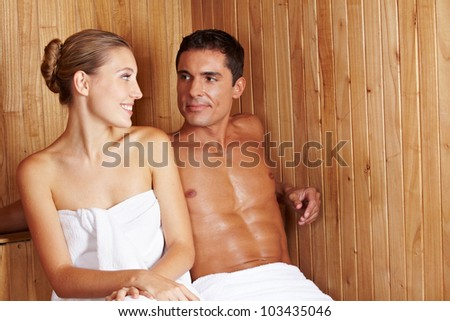 Happy woman and man sitting together in a sauna - stock photo