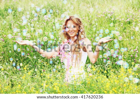 Happy woman and soap bubbles in green summer meadow - stock photo