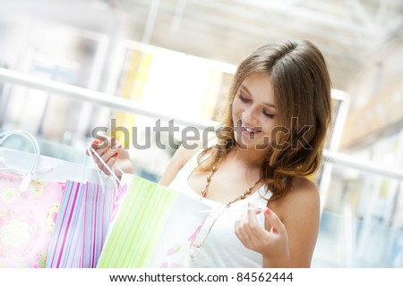Happy woman at a shopping center with bags. Seasonal preparty shopping boom