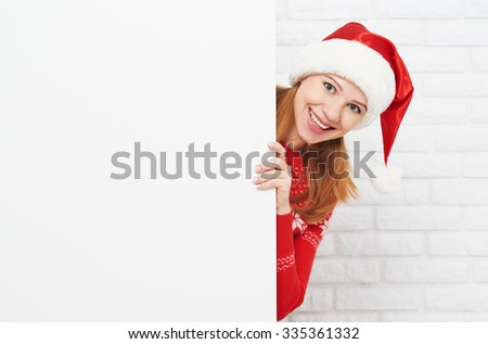 happy woman at Christmas with an blank empty white poster - stock photo