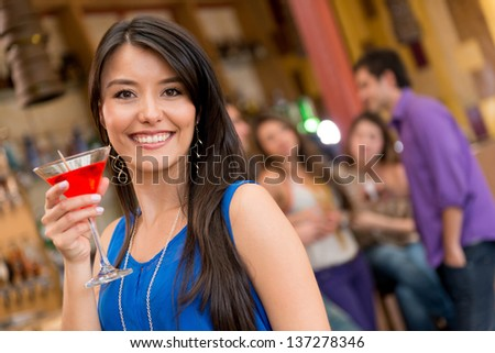 Happy woman at the club having drinks with her friends - stock photo