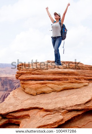 Happy woman at the Grand Canyon with arms up - stock photo
