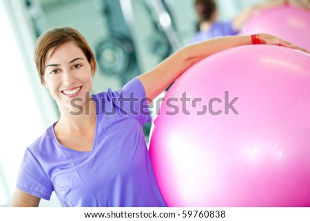 Happy woman at the gym with a pilates ball - stock photo