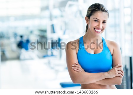 Happy woman at the gym with arms crossed - stock photo