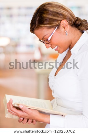 Happy woman at the library reading a book