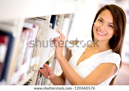 Happy woman at the library taking a book