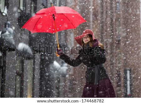 Happy woman at winter day with red umbrella - stock photo