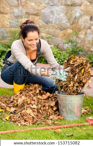 Happy woman autumn putting dry leaves bucket backyard cleaning garden - stock photo