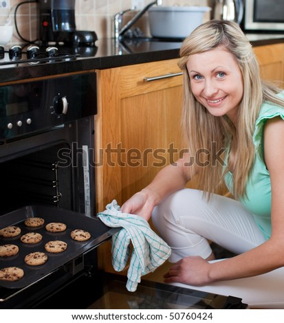 Happy woman baking cookies in the kitchen