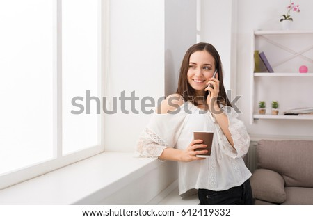 Happy woman calling on mobile phone standing near window at home, drink coffee, copy space