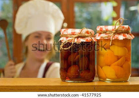 Happy woman chef with homemade canned fruit - focus on the jars - stock photo