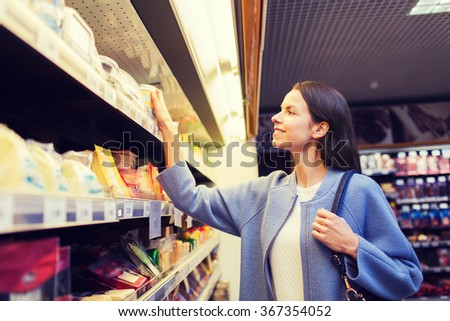 happy woman choosing and buying food in market - stock photo