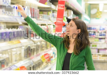 Happy woman choosing products in supermarket - stock photo