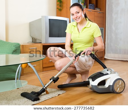 Happy woman cleaning an apartment floor with a vacuum cleaner - stock photo