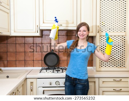 Happy woman cleaning kitchen. Beautiful girl with cleaning spray wearing protective gloves showing muscular strength. - stock photo