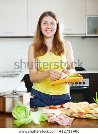Happy woman cooking sandwiches with cheese and  hamon in her kitchen