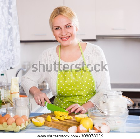 Happy woman cooking tasty apple pie at home - stock photo