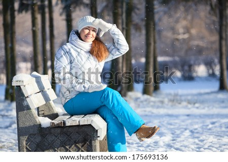 Happy woman covering eyes from sunlight at winter, copyspace - stock photo