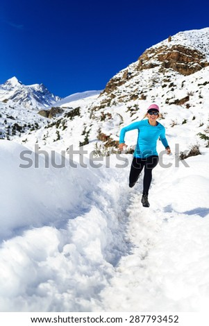 Happy woman cross country trail running in beautiful inspiring mountains landscape. Healthy lifestyle, fitness and exercising outdoors in winter nature. Inspiration and motivation be healthy fit. - stock photo
