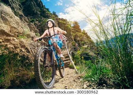 Happy woman cyclist rides in the mountains on a mountain bike. Portrait of a smiling girl on a bicycle traveling. Adventure travel. - stock photo