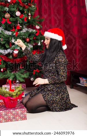 Happy woman decorate Christmas tree with ball home and sitting down - stock photo