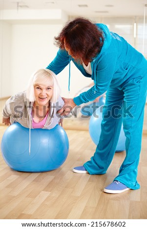 Happy woman doing physical exercise with fitness ball in sport gym  - stock photo