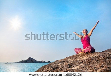 Happy woman doing yoga in red costume on the stone near the ocean in India - stock photo