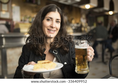 Happy woman drinking beer in bar with ambient and natural lightning - stock photo