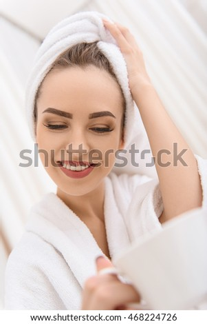 Happy woman drinking beverage at spa