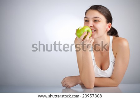 Happy woman eating a green apple smiling - stock photo