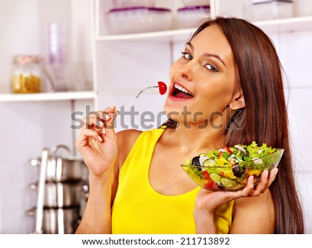 Happy woman eating salad at kitchen. - stock photo