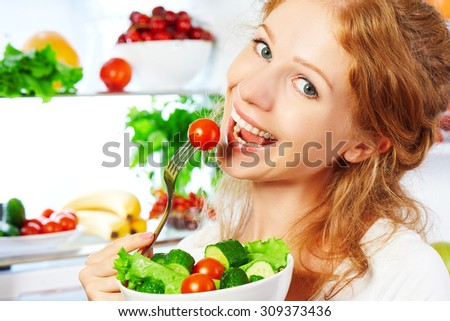 happy woman eats healthy food vegetable vegetarian salad about refrigerator - stock photo