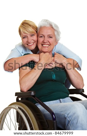 Happy woman embracing disabled senior woman in wheelchair - stock photo