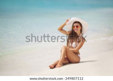 Happy woman enjoying beach relaxing joyful in summer by tropical blue water. Beautiful bikini model happy on travel wearing beach sun hat on Hapuna beach, Big Island, Hawaii, USA. - stock photo