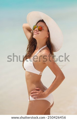Happy woman enjoying beach relaxing joyful in summer by tropical blue water. Beautiful white bikini model happy on travel wearing beach sun white hat on ocean beach, Big Island, Hawaii, USA. - stock photo
