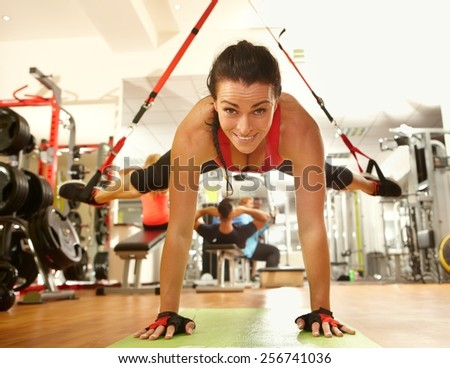 Happy woman enjoying hard suspension training in gym. - stock photo