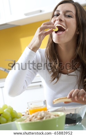 Happy woman enjoying her healthy breakfast - stock photo