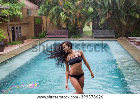 Happy woman enjoying in black swimsuit under tropical rain near luxury swimming pool - stock photo