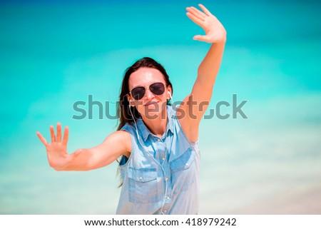 Happy woman enjoying listen music on white sandy beach - stock photo