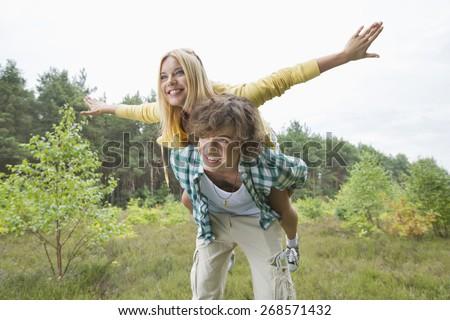 Happy woman enjoying piggyback ride on man in forest - stock photo