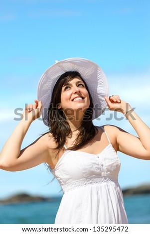 Happy woman enjoying summer vacation on beach. Beautiful caucasian girl smiling. Playa de Verdicio, Asturias, Spain. - stock photo